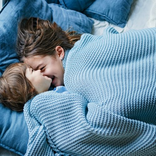 Happy siblings snuggling under warm knitted blanket. Little boy and his teenager sister enjoying staying at home at cold winter day having fun together, Family quality time on holidays.