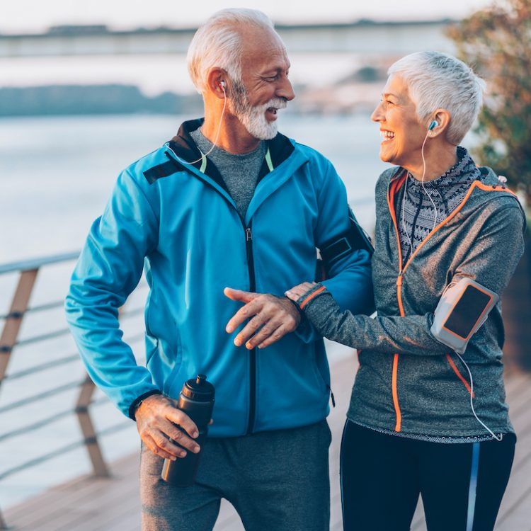 Senior couple in sports clothing and sports technologies jogging together across the bridge