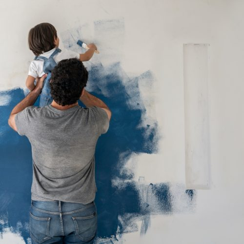 Boy helping his father painting the house