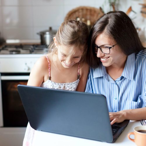 Holiday shopping online. Happy mother and child girl make purchases in the Internet on Black Friday. Cute kid and woman are smiling. Family are enjoying buying gifts with laptop in cozy home kitchen.
