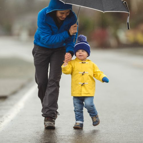 Young mom doesn't let the rain stop her from taking her young boy on a joyful walk